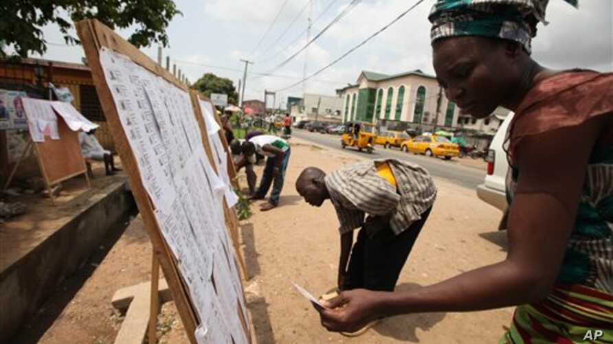 Residents check for their names on the voters registration list in Lagos, Nigeria, Feb. 18, 2011