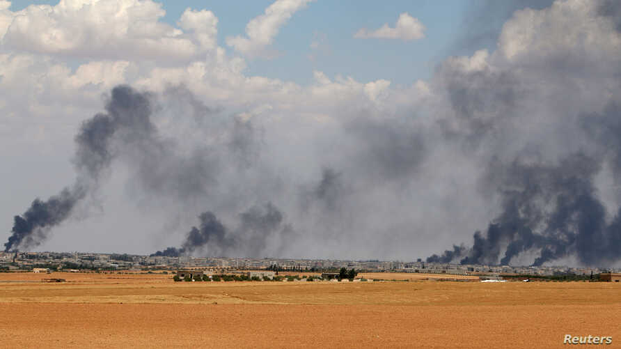 Smoke rises from Manbij city, Aleppo province, Syria, June 8, 2016.