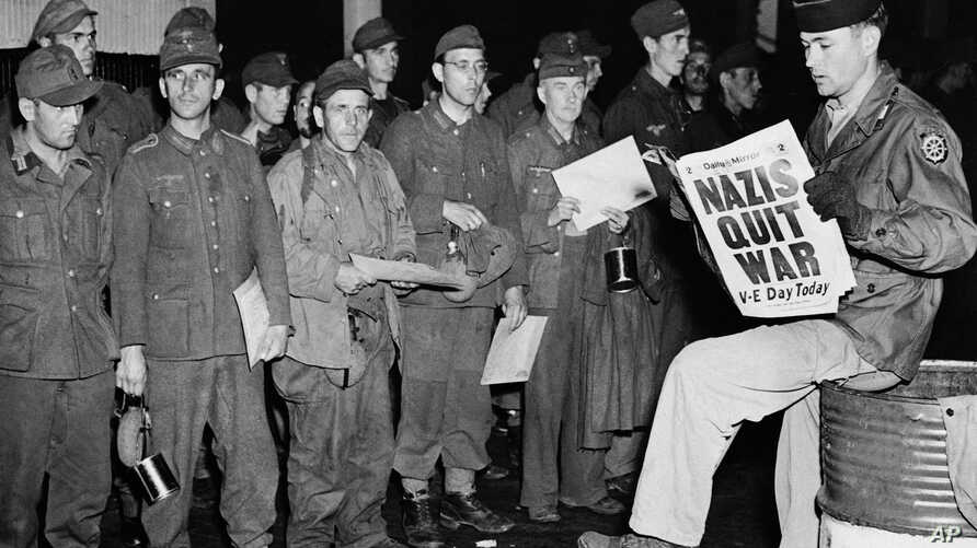 Pfc. Clarence K. Ayers of Evansville, Ind., reads the news of V-E Day as newly arrived German prisoners stand of a New York City pier, May 8, 1945.