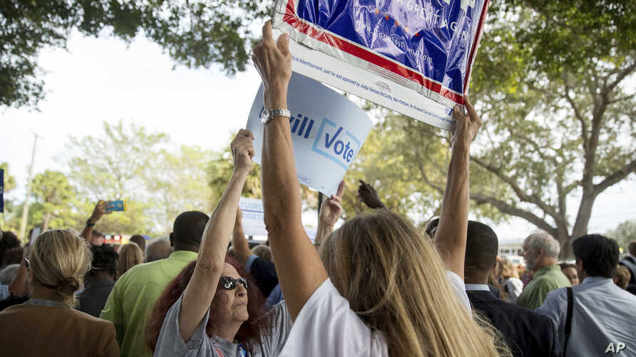 A supporter of Democratic presidential candidate Hillary Clinton attempts to block a Republican presidential candidate Donald Trump supporter from waving a sign as Clinton greets supporters outside an early voting station at the Pompano Beach Amphith