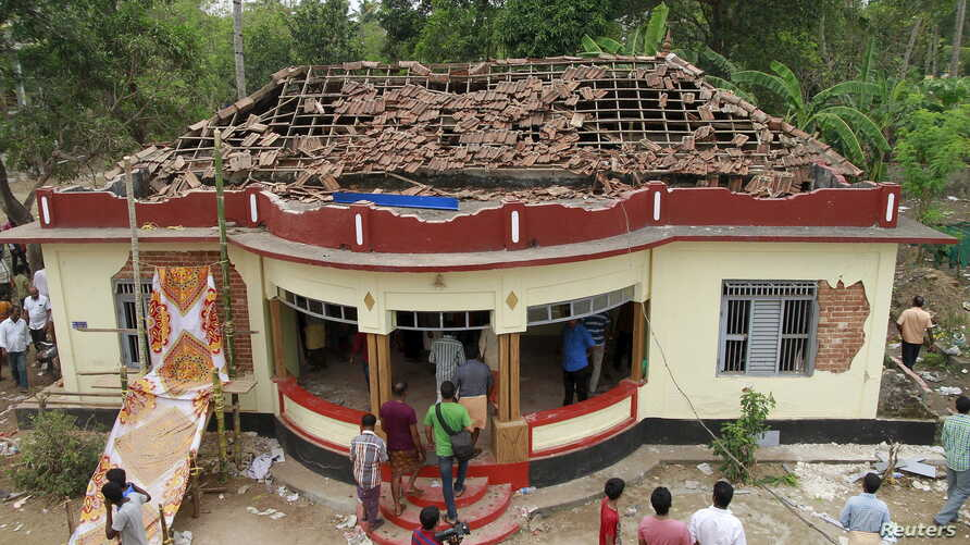 People gather around a damaged section of a temple after a fire broke out at a temple in Kollam in the southern state of Kerala, India, April 10, 2016.