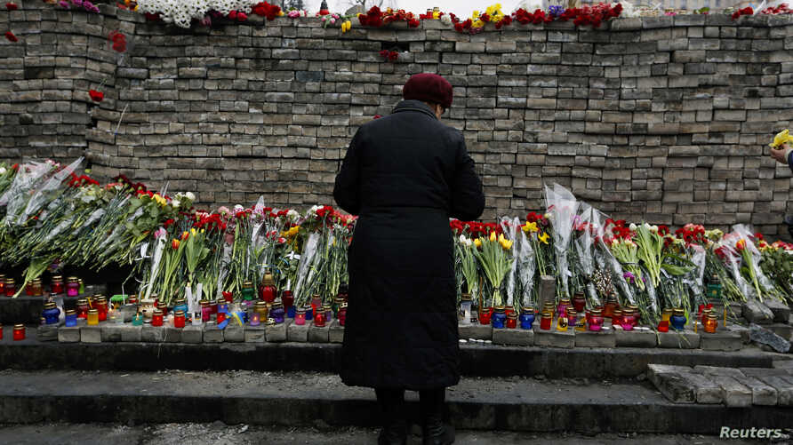"""FILE - A woman mourns before a memorial to those killed in violence in Kiev, Feb. 25, 2014 — the day that Ukraine's parliament voted to send fugitive President Viktor Yanukovich to be tried by the International Criminal Court for """"serious crimes"""" com"""