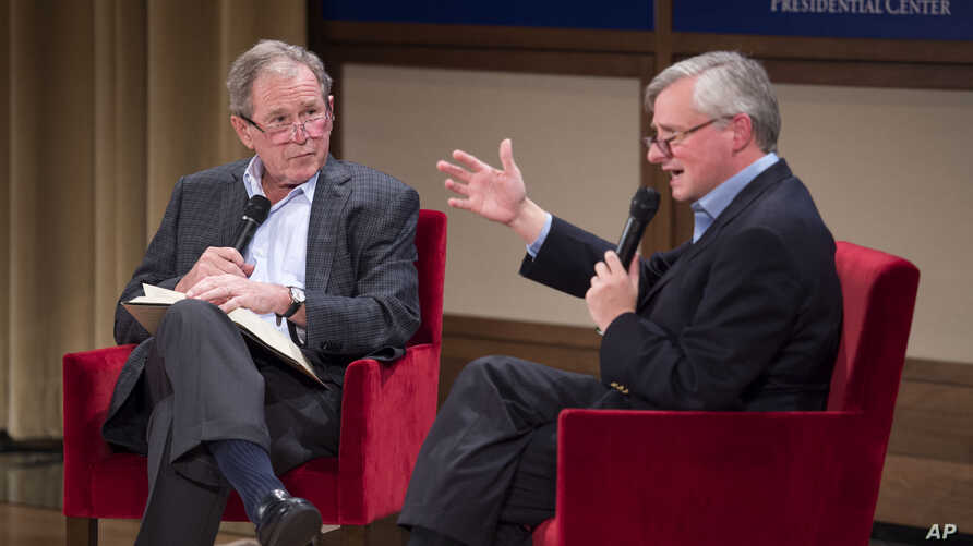 Former President George W. Bush, left, listens to Pulitzer Prize winning author Jon Meacham, right, talk about his biography of Bush's father, former President George H. W. Bush, Sunday, Nov. 8, 2015.