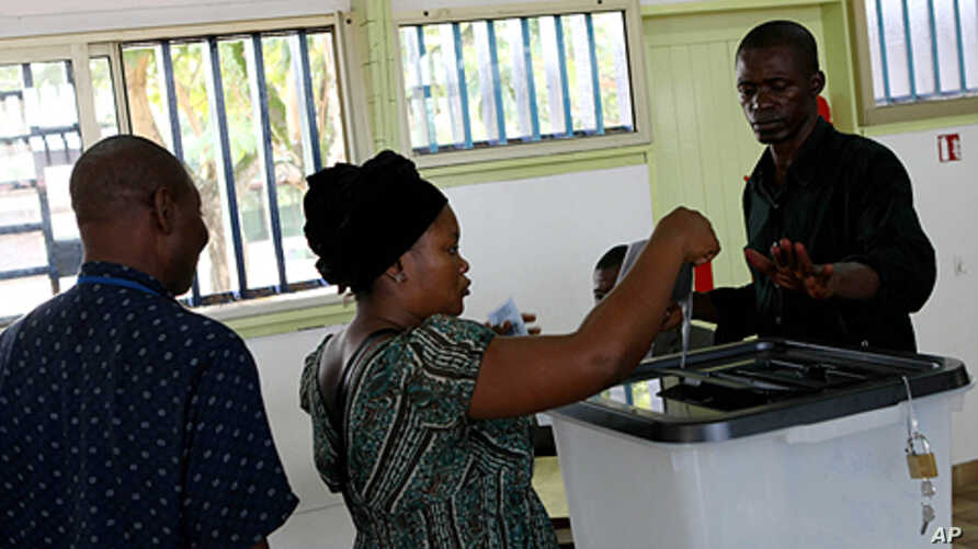 A woman casts her vote at the Ba Oumar school voting station of Libreville, Gabon, December 17, 2011.