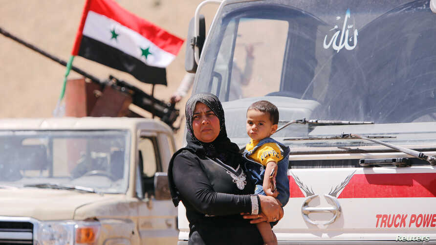 FILE - A Syrian refugee who left Lebanon carries a toddler as she arrives in Qalamoun, Syria, June 28, 2018.