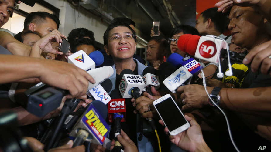 Maria Ressa, center, the award-winning head of a Philippine online news site Rappler, talks to the media after posting bail at a Regional Trial Court following an overnight arrest by National Bureau of Investigation agents on a libel case Thursday, F