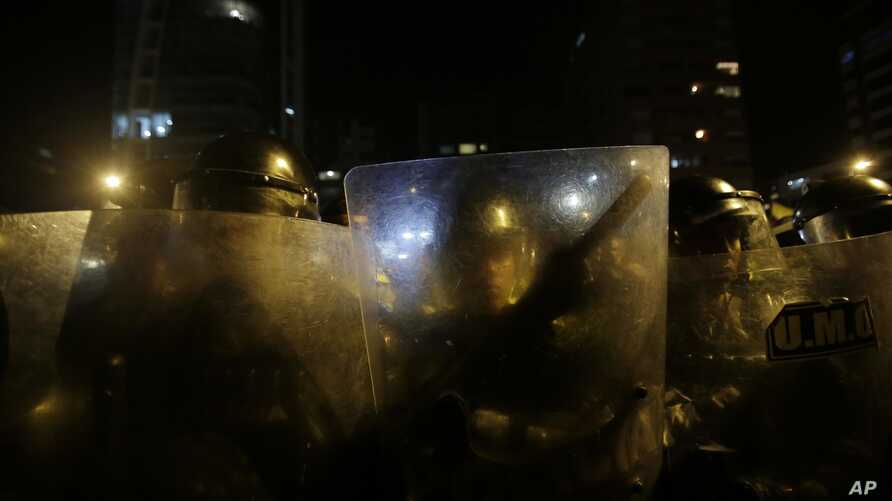 Police form a barricade as people protests against a law debated by the National Assembly that would raise taxes as land prices appreciated, in Quito, Ecuador, Thursday, Dec. 8, 2016.