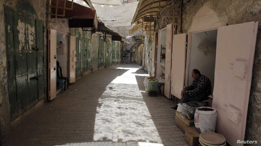 FILE - A Palestinian shop owner waits for customers at his shop in a market in the Old City of the West Bank town of Hebron.