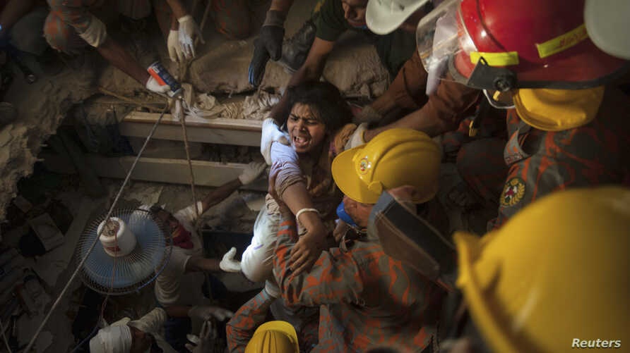 Rescue workers rescue a garment worker from the rubble of the collapsed Rana Plaza building, in Savar, 30 km (19 miles) outside Dhaka April 27, 2013. Two factory bosses and two engineers were arrested in Bangladesh on Saturday, 72 hours after the col