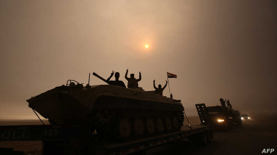 Iraqi forces flash the V-sign as they drive through the Al-Shura area, south of Mosul, Oct. 24, 2016, during an operation to retake the main hub city from the Islamic State (IS) group.
