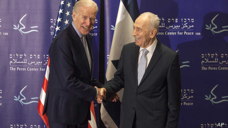 Former Israeli President Shimon Peres, right, and U.S. Vice President Joe Biden shake hands during their meeting at the Peres Center for Peace in Jaffa, March 8, 2016.