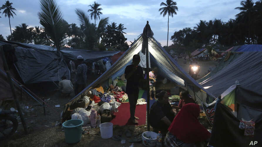 Villagers gather at a temporary shelter after fleeing their damaged village affected by Sunday's earthquake in North Lombok, Indonesia, Aug. 8, 2018.