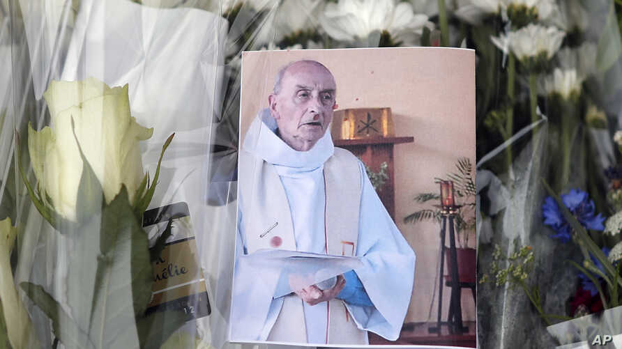 A picture of late Father Jacques Hamel is placed on flowers at the makeshift memorial in front of the city hall closed to the church where an hostage taking left a priest dead the day before in Saint-Etienne-du-Rouvray, Normandy, France, July 27, 201
