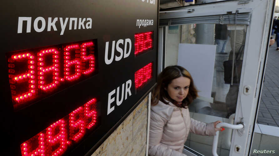 A woman walks out of a building past a board showing currency exchange rates in St. Petersburg, Russia, Sept. 26, 2014.