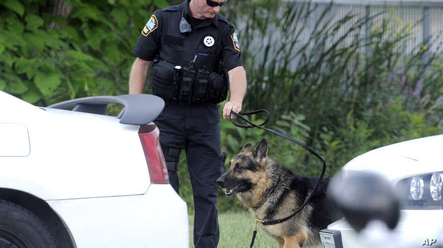A police K-9 team takes a break in the search for suspects in the shooting of a police officer in Fox Lake, Ill., Sept. 1, 2015.