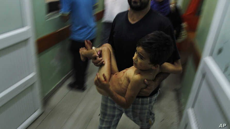 A Palestinian man carries a child, wounded in an Israeli strike on a compound housing a U.N. school in Beit Hanoun, in the northern Gaza Strip, into the emergency room of the Kamal Adwan hospital in Beit Lahiya, July 24, 2014.