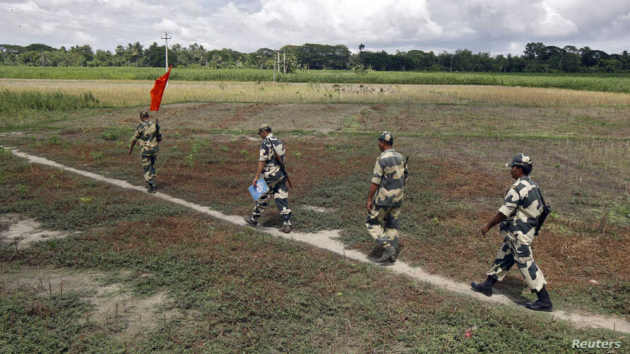 FILE -  Indian Border Security Force soldiers walk across the open border with Bangladesh to attend a flag meeting in West Bengal, India, June 20, 2015. Indian officials said Sept. 23, 2017, that because of security risks, border forces have been aut