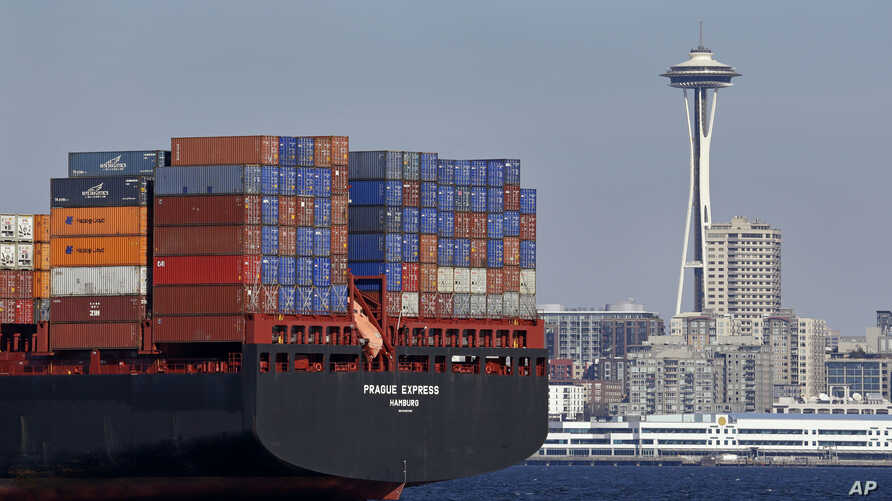 FILE - In this Feb. 15, 2015, file photo, the Space Needle towers in the background beyond a container ship anchored in Elliott Bay near downtown Seattle.