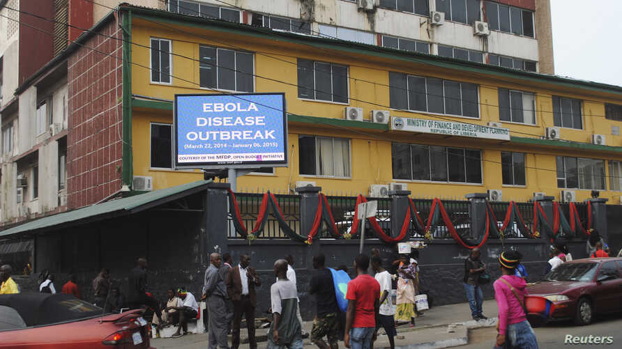 """Pedestrians walk past a sign reading """"Ebola disease outbreak"""" outside the Ministry of Finance in Monrovia, Liberia, Jan. 12, 2015."""