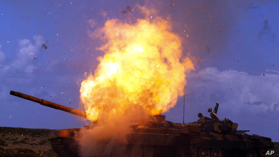 A tank belonging to forces loyal to Libyan leader Muammar Gaddafi explodes after an air strike by coalition forces, along a road between Benghazi and Ajdabiyah March 20, 2011.