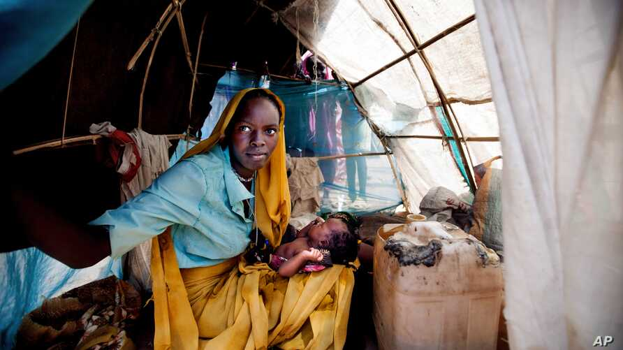 FILE - Aid workers have expressed alarm at poor conditions in South Sudan refugee camps. A woman and baby shelter in a makeshift tent at the Kalma refugee camp in this photo released by the United Nations African Union Mission in Darfur, Sudan, March