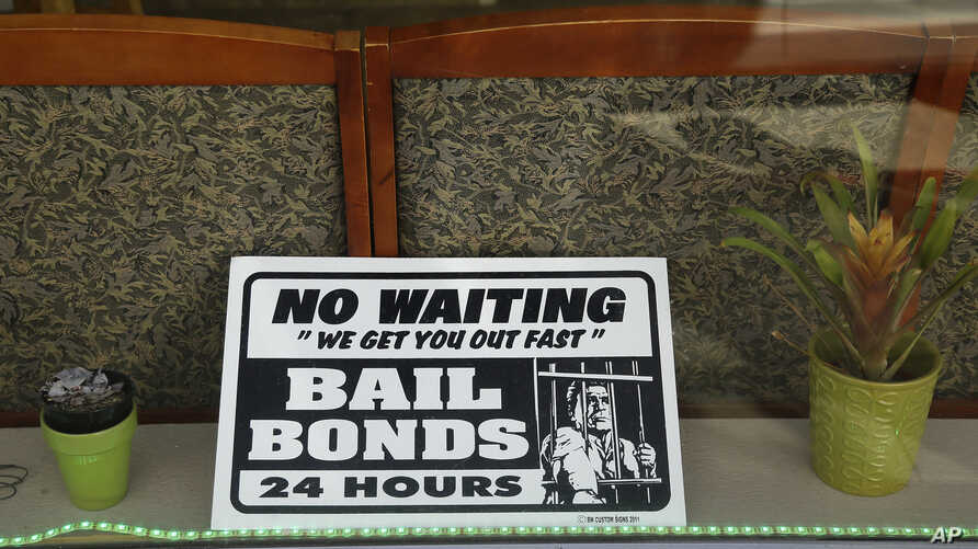 FILE - A sign is seen in the window of a bail bonds office across from the Hall of Justice in San Francisco, Dec. 23, 2015.