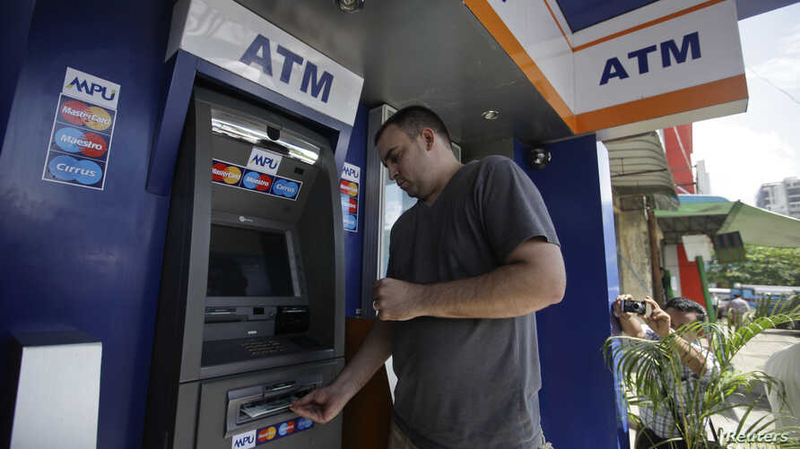 American tourist Ryan Russell withdraws cash from an ATM machine using a MasterCard card, the first such ATM transaction, Rangoon, Burma, November 15, 2012.