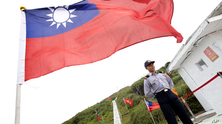 FILE - A Taiwan Coast Guard officer stands guard under a Taiwanese flag in the East China Sea, north of Taiwan, April 9, 2016.