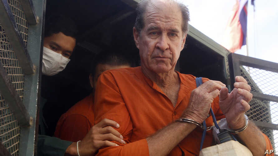 Australian filmmaker James Ricketson, right, is helped off a prisoner truck upon his arrival at Phnom Penh Municipal Court in Phnom Penh, Cambodia, Aug. 29, 2018.