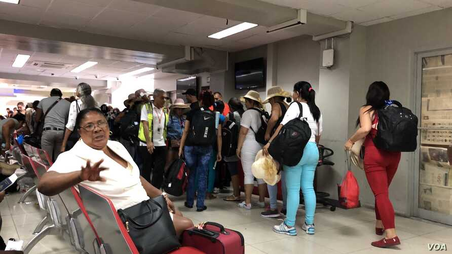 Cuban tourists line up to board their flight at the Toussaint Louverture airport in Port-au-Prince, Haiti. (S. Lemaire/VOA)