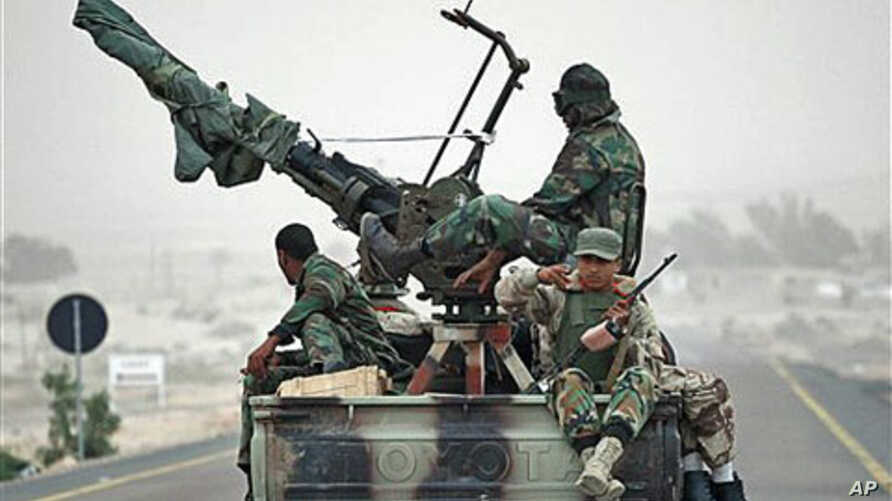 Libyan rebels who are part of the forces against Libyan leader Moammar Gadhafi ride in a truck carrying an anti-aircraft gun on their way to the front-line near Ras Lanuf, west of the town of Brega, eastern Libya, March 4, 2011