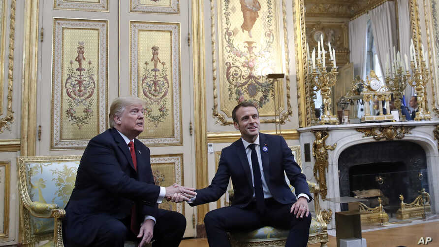 President Donald Trump shakes hands with French President Emmanuel Macron inside the Elysee Palace in Paris Saturday Nov. 10, 2018.