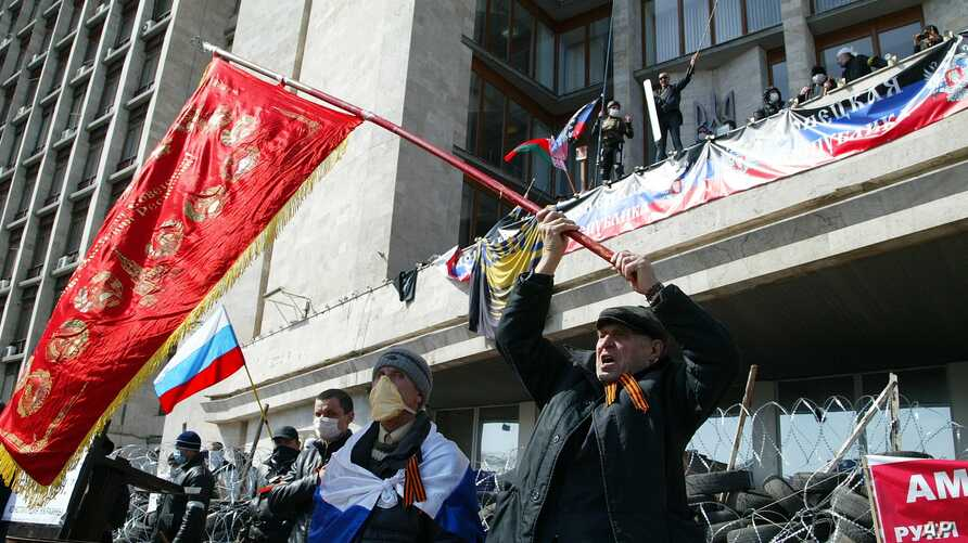 Activists wave an old Soviet and Russian national flags in front of a barricade at the regional administration building, in Donetsk, Ukraine, April 7, 2014.