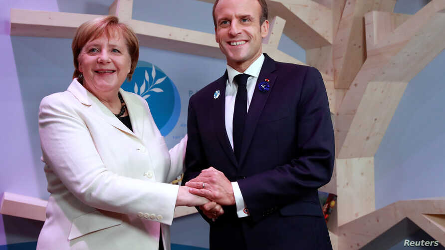 German Chancellor Angela Merkel and French President Emmanuel Macron hold hands after leaving  books at the peace library at the Paris Peace Forum as part of the commemoration ceremony for Armistice Day, 100 years after the end of World War I, in Par