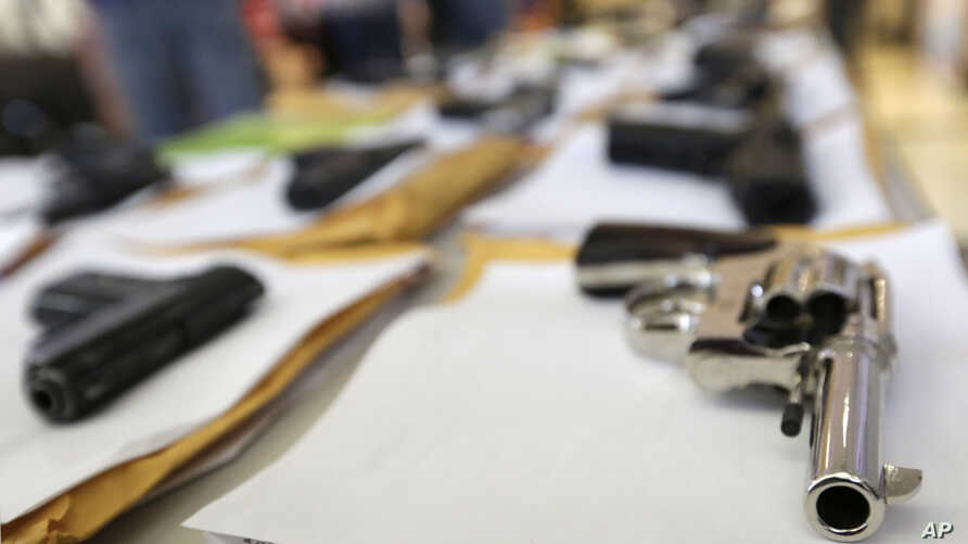 FILE - Chicago police display some of the thousands of illegal firearms they have confiscated in 2014 in their battle against gun violence in Chicago, July 7, 2014.
