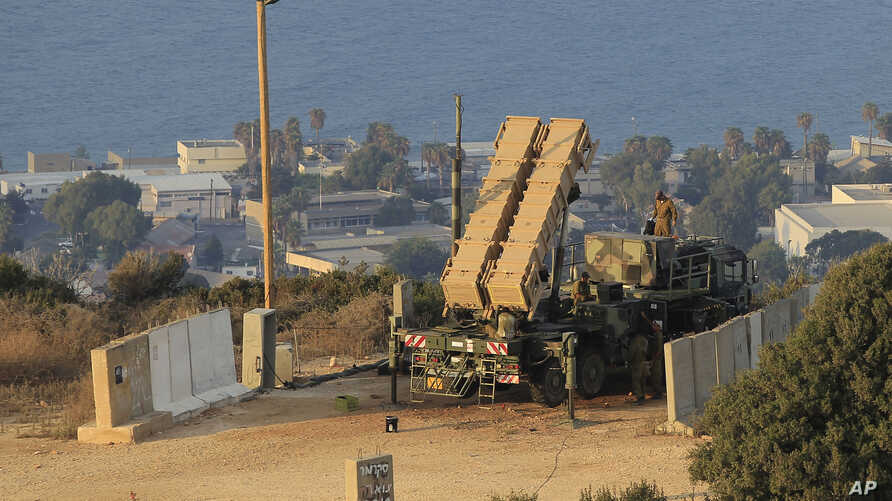 FILE - Israeli soldiers are seen next to a Patriot rocket interceptor battery deployed in the northern Israeli city of Haifa.