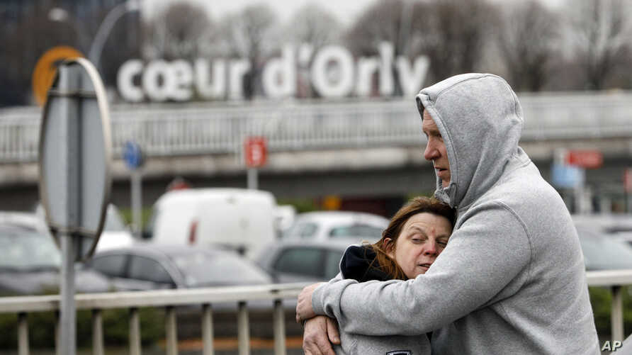 Travelers hug outside Orly Airport, south of Paris, March, 18, 2017. A man was shot to death Saturday after trying to seize the weapon of a soldier guarding Paris' Orly Airport, prompting a partial evacuation of the terminal, police said.
