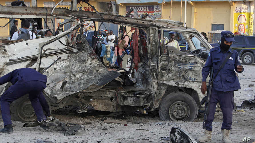 Security forces stand near the wreckage of a minibus at the scene of a car bomb attack in Mogadishu, Somalia, Sept. 28, 2017.