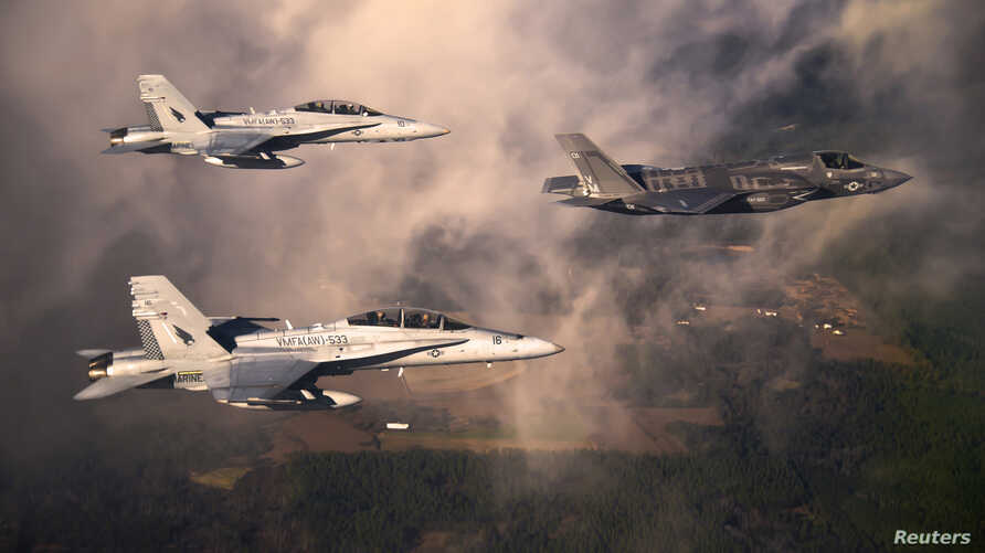 A U.S. Marine Corps F-35 Lightening II multirole fighter jet (R) is escorted by two USMC F-18 Hornets as it flies towards Eglin Air Force Base, Florida in this U.S. Air Force handout photo dated January 11, 2012. The Pentagon is preparing to lift a ""