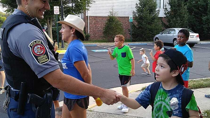 A boy shakes the hand of police officer Anthony Patalena in Fairfax Country, Virginia, Aug. 2, 2016. (D. Block/VOA)