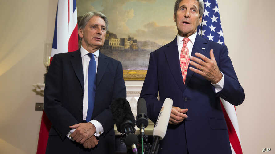 US Secretary of State John Kerry, right, answers a question about the ongoing crisis in Syria during a news conference with British Foreign Secretary Philip Hammond, Sept. 19, 2015, in London.