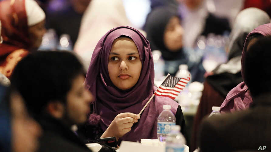 A young woman waves an American flag along with others at the beginning of a Muslim conference against terror and hate at the Curtis Culwell Center, Jan. 17, 2015, in Garland, Texas.