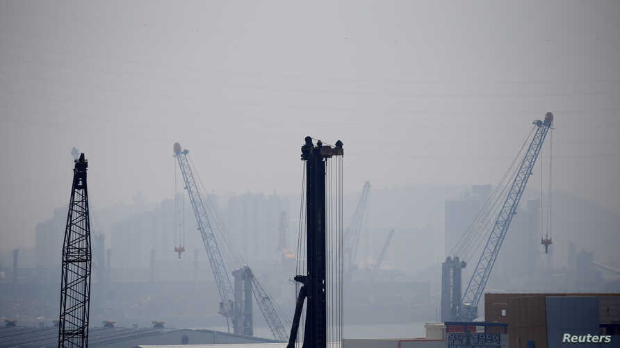 FILE - Cranes are seen on a polluted day in Incheon, South Korea, May 30, 2016.