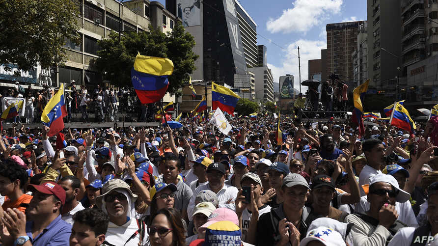 Supporters of Venezuelan opposition leader and self declared acting president Juan Guaido take part in rally to press the military to let in US humanitarian aid, in eastern Caracas on Feb. 12, 2019.