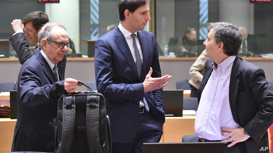 Dutch Finance Minister Wopke Hoekstra, center, speaks with Greek Finance Minister Euclid Tsakalotos, right, and Italian Finance Minister Pier Carlo Padoan, left, during a meeting of EU finance ministers at the Europa building in Brussels, March 13, 2