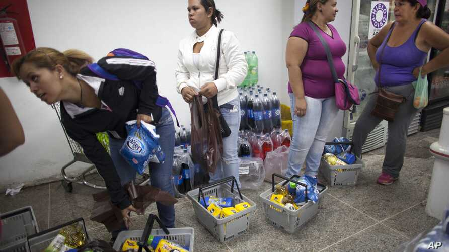 FILE - Shoppers wait in line to check out at a supermarket in the Propatria neighborhood of Caracas, Venezuela.