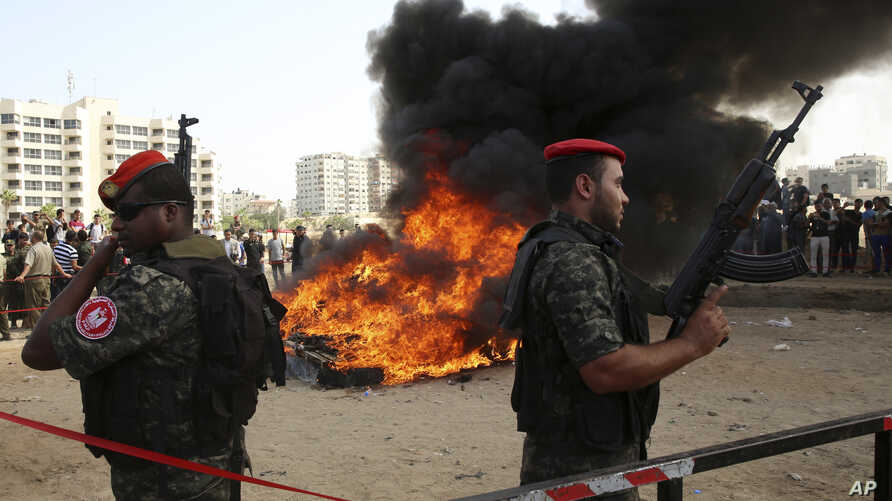 Hamas security forces stand guard while they burn some 1,383 bars of hashish and 1,242,000 pills of Tramadol, that have been seized since the beginning of the year, before they burn it, in Gaza City, Monday, Oct. 22, 2018.