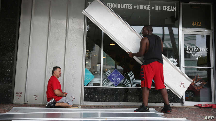 Jason Brock (L) and Kevin Hunter put up hurricane shutters in front of a business as Hurricane Matthew approaches the area on Oct. 6, 2016 in Delray Beach, United States.