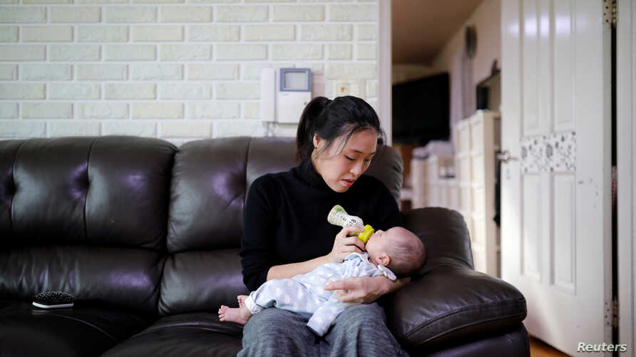 Kim Mi-sung feeds her baby son at their home in Seoul, South Korea, Dec. 19, 2018.