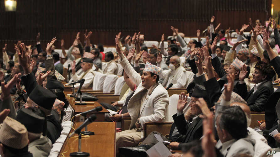 Nepalese lawmakers raise their hands as they begin voting on a draft of the new constitution at the Constituent Assembly Hall in Kathmandu, Nepal, Sept. 13, 2015.
